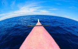 Schöner gebogener blauer Himmel, der auf einem Boot sitzt Stockbilder