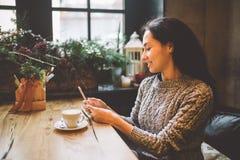 Schöner Gebrauch des jungen Mädchens, Arten simst an einem Handy an einem Holztisch nahe dem Fenster und trinkt Kaffee in einem C Stockbilder