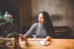 Schöner Gebrauch des jungen Mädchens, Arten simst an einem Handy an einem Holztisch nahe dem Fenster und trinkt Kaffee in einem C Stockfoto