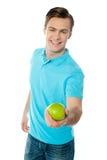 Schöner gesunder Kerl, der einen grünen Apfel anbietet stockbild