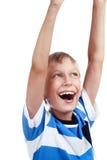 Schöner glücklicher blonder Junge, der sein Handaufwärts Tanzen und -c$lachen anhebt Stockfoto