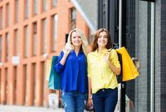 Schöner glücklicher Brunette und blondes gehendes Händchenhalten Lizenzfreies Stockfoto