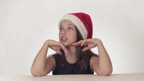 Schöner glücklicher Mädchenjugendlicher in einem Santa Claus-Hut drückt emotional ein Erstaunen auf weißer Hintergrundvorratgesam stock video