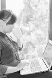 Schöner glücklicher Student mit einem Laptop, der gegen Fenster sitzt Stockbild