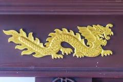 Schöner goldener Drache machte Muster auf hölzernem Schaukasten in Handarbeit Lizenzfreie Stockbilder