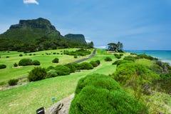 Schöner grüner Golfplatz durch das Meer Stockbild