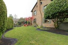 Schöner grüner Hinterhof mit Hecke und exotischem rotem Baum stockbilder