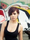 Schöner Graffitihintergrund der jungen Frau Stockfotografie