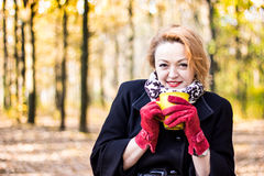 Schöner Griff der jungen Frau ein Tasse Tee und Versuch, zum im Herbstpark warm zu erhalten Stockfotos