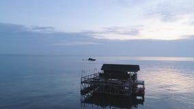 Schöner hölzerner Bungalow umgeben durch atemberaubendes Ozeanwasser schuß Betäubungsmeerblick mit blauem Himmel und kleines stock video
