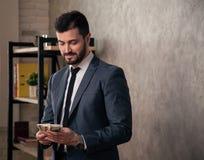 Schöner hübscher Geschäftsmann im Büro, das seinen Schreibtisch bereitsteht und Geld zählt tragender Anzug und eine Bindung lizenzfreies stockfoto