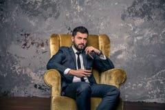 Schöner hübscher Geschäftsmann macht eine Pause, die auf dem Stuhl und dem trinkenden Whisky mit einer Zigarre und einem Denke stockfotografie