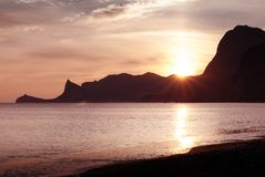 Schöner heller Sonnenuntergang auf dem Schwarzen Meer im Sudak Küste mit Entwurf des Kaps Kapchik Blauer Himmel und blanke Hügel Lizenzfreie Stockfotos