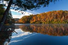 Schöner Herbstmorgen mit reflektierendem See und Bäumen Lizenzfreie Stockbilder