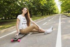 Schöner Hippie des jungen Mädchens mit dem langen Haar, das auf einem longboard Skateboard fahren sitzt Stockfoto