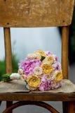 Schöner Hochzeitsblumenstrauß auf einem hölzernen schäbigen Stuhl Lizenzfreie Stockbilder