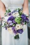 Schöner Hochzeitsblumenstrauß in den Händen der Braut Stockbild