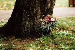 Schöner Hochzeitsblumenstrauß nahe dem Baum Stockfoto
