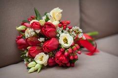 Schöner Hochzeitsblumenstrauß von den roten Tulpen, die auf dem Sofa liegen Stockfotografie