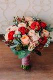 Schöner Hochzeitsblumenstrauß von roten Blumen, von rosa Blumen und von Grün ist auf dem Bretterboden stockbild
