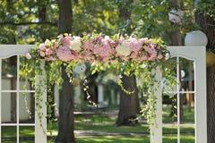 Schöner Hochzeitsbogen, verziert mit Rosen und Peons, Nahaufnahme Stockbild