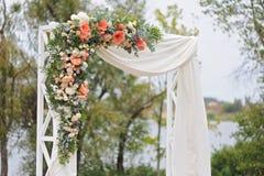 Schöner Hochzeitsbogen, verziert mit weißem Stoff und Blumen, Nahaufnahme Stockbild