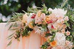 Schöner Hochzeitstorbogen Bogen verziert mit pfirsichfarbenem Stoff und Blumen Stockbild