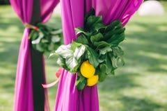 Schöner Hochzeitstorbogen Bogen verziert mit purpurrotem Stoff und Zitrone stockbilder