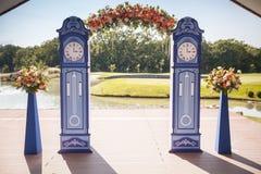 Schöner Hochzeitstorbogen Bogen wie die Uhren verziert mit pfirsichfarbenen Blumen lizenzfreie stockfotografie