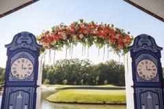 Schöner Hochzeitstorbogen Bogen wie die Uhren verziert mit pfirsichfarbenen Blumen lizenzfreies stockfoto