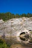 Schöner hoher Felsen auf dem Fluss stockbild