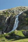 Schöner hoher Gebirgswasserfall mit Steinen Stockfoto
