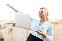 Schöner intelligenter Geschäftsdamenstand auf dem Dach mit Laptop in h Stockfoto