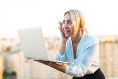 Schöner intelligenter Geschäftsdamenstand auf dem Dach mit Laptop in h Lizenzfreies Stockbild