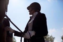 Schöner Jockeymädchenstand nahe bei ihrem Pferd Lizenzfreies Stockbild