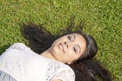 Schöner Jugendlicher, der auf dem Gras liegt Lizenzfreie Stockbilder