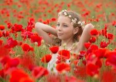 Schöner Junge auf dem roten Mohnblumengebiet Stockfotos