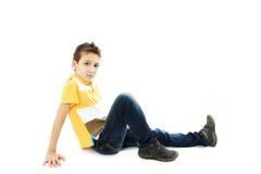 Schöner Junge, der auf Fußboden sitzt stockbild