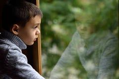 Schöner Junge, der heraus Fenster schaut Lizenzfreies Stockbild