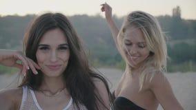 Schöner junge Frau Brunette und ihr blondes Freundtanzen, die im Urlaub Spaß lächelt und hat stock video