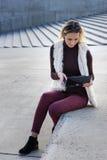 Schöner junge Frauen-Abschluss oben Blondes Mädchen sitzt auf Schritten außerhalb eines Büros und hält eine Tablette Frau mit Not Lizenzfreie Stockfotos