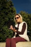 Schöner junge Frauen-Abschluss oben Blondes Mädchen sitzt auf Schritten außerhalb eines Büros und hält eine Tablette Frau mit Not Lizenzfreie Stockfotografie
