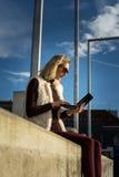 Schöner junge Frauen-Abschluss oben Blondes Mädchen sitzt auf Schritten außerhalb eines Büros und hält eine Tablette Frau mit Not Lizenzfreies Stockfoto