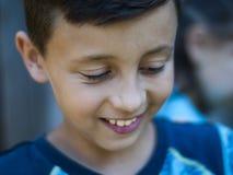 Schöner Jungenteenager mit dem dunklen Haar, das nah herauf Porträt lächelt stockbilder