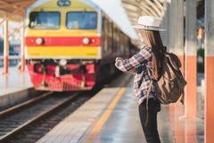 Schöner junger asiatischer Frauenreisender, der Uhr mit brauner Tasche, Wartezug am Bahnhof, chinesische Touristen, Reise schaut stockbild
