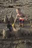 Schöner junger blonder Junge, der auf Strand in einem Sandburg spielt Stockfotos