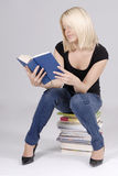 Schöner junger blonder Kursteilnehmer, der auf Büchern sitzt Lizenzfreie Stockfotografie