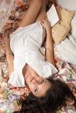Schöner junger Brunette, der auf Bett mit Buch liegt Stockfotografie