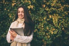 Schöner junger Brunette, der auf gefallenen Herbstlaub in einem Park, ein eBook auf einem Tablet-Computer lesend sitzt stockbilder