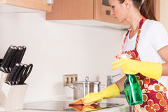 Schöner junger Brunette, der die Küche säubert. Lizenzfreie Stockfotos